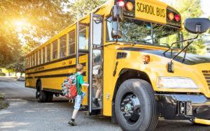 School Bus Contractors Insurance - Young Kid Getting On A Schoolbus